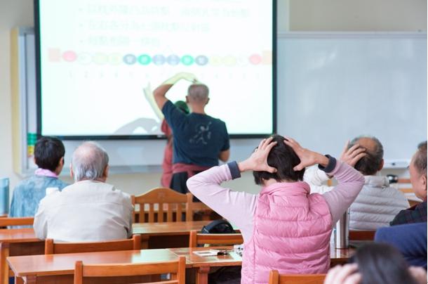 學生們跟隨老師教授的方式為頭部按摩,藉此改善頭痛問題。